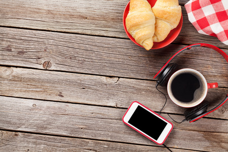 coffee table: Fresh croissants, coffee, smartphone and headphones on wooden table. Top view with copy space Stock Photo