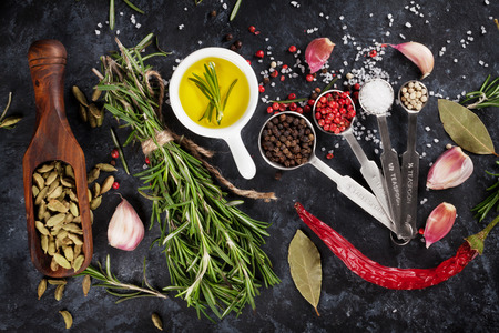 Herbs and spices over black stone background. Top view