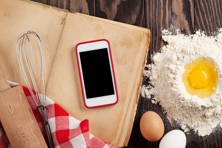Kitchen table with ingredients, utensils and smartphone with blank screen for your app over cooking book on wooden table. Top view Imagens