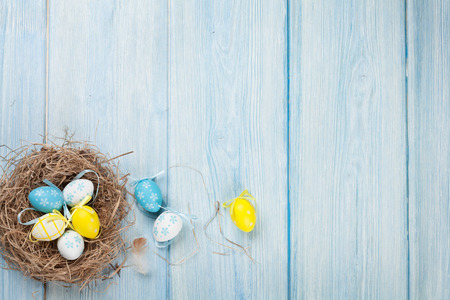 Easter background with eggs in nest over blue wooden table. Top view with copy space