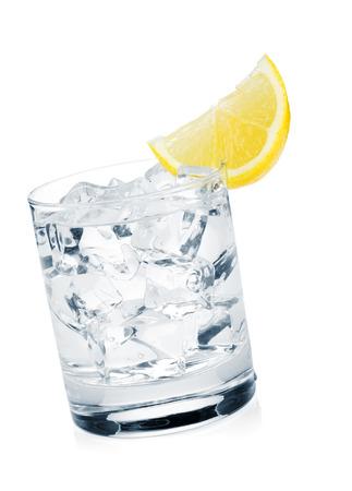 Glas zuiver water met ijsblokjes en schijfje citroen. Geïsoleerd op witte achtergrond