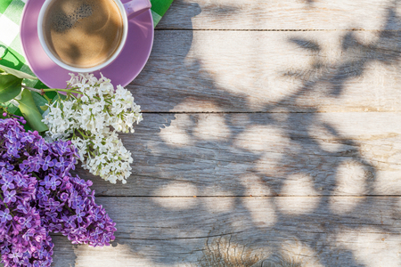 Coffee cup and colorful lilac flowers on garden table. Top view with copy space Stockfoto