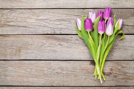 tulip: Fioletowe tulipany na drewnianym stole. Widok z góry z miejsca na kopię