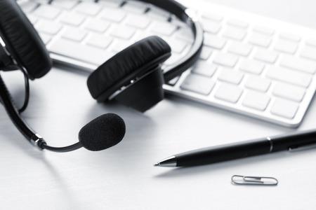 recepcionista: escritorio de oficina con auriculares y PC. Llame a la mesa de soporte central. tonos azules