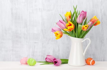huevo blanco: Easter eggs and colorful tulips bouquet on shelf in front of wooden wall. View with copy space