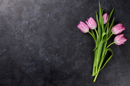 Fresh pink tulip flowers on dark stone table. Top view with copy space