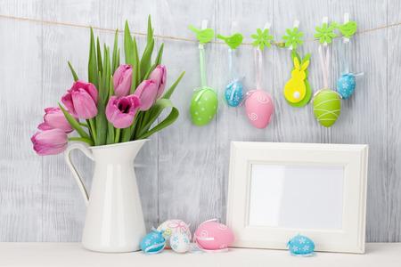イースターの卵、空白のフォト フレーム、木製壁の前に棚の上のピンクのチューリップの花束。コピー スペースを表示します。 写真素材