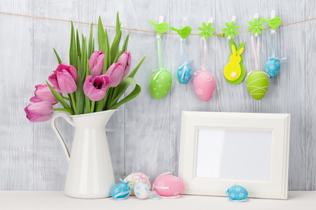 Easter eggs, blank photo frame and pink tulips bouquet on shelf in front of wooden wall. View with copy space