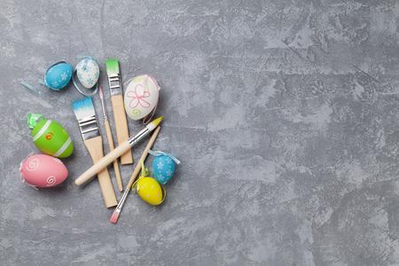 huevos de pascua: huevos de pascua de colores y pinceles en la mesa de piedra. Vista superior con espacio de copia