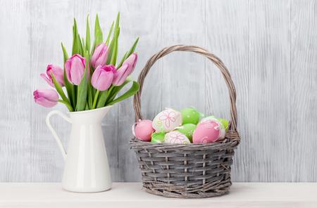 osterei: Ostereier im Korb und Tulpen auf dem Regal vor Holzwand
