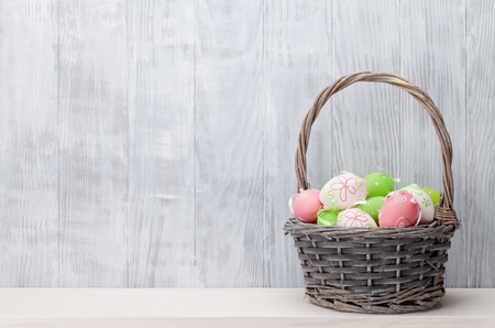 baskets: Easter eggs in basket on shelf in front of wooden wall. View with copy space