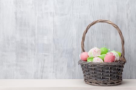 Huevos de Pascua en cesta en el estante delante de la pared de madera. Ver con espacio de copia