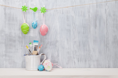 Colorful easter eggs and brushes on shelf in front of wooden wall. View with copy space