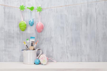 estanterias: Huevos de Pascua coloridos y pinceles sobre estante en frente de la pared de madera. Ver con espacio de copia