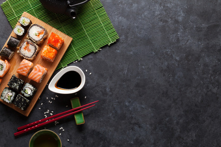 Set of sushi maki and green tea on stone table. Top view with copy space