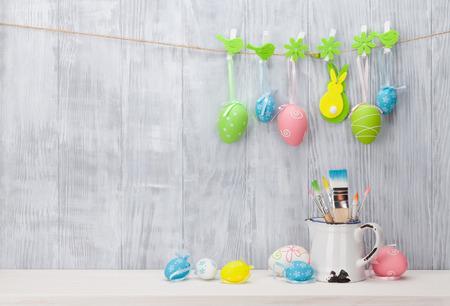 Coloridos huevos de Pascua y pinceles en el estante en frente de la pared de madera. Vista con espacio de copia