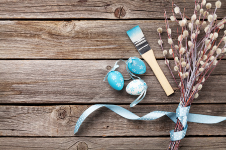 white color: Colorful easter eggs and pussy willow on wooden table. Top view with copy space Stock Photo