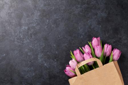 flowers: Frescas flores de tulipanes de color rosa en bolsa de papel en la mesa de piedra oscura. Vista superior con espacio de copia