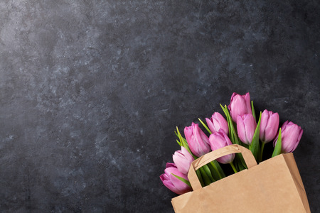 Fresh pink tulip flowers in paper bag on dark stone table. Top view with copy space