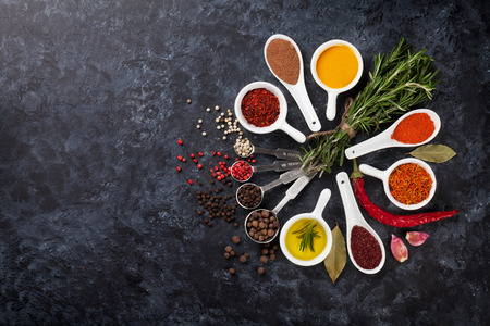 condiments: Herbs, condiments and spices on stone background. Top view with copy space