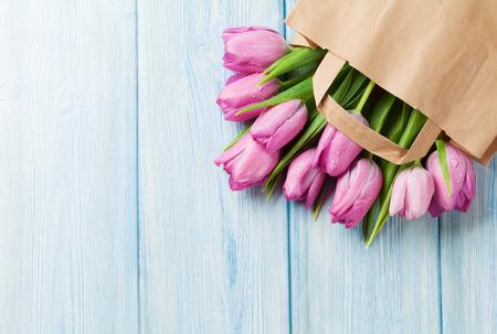 Verse roze tulp bloemen in een papieren zak op houten tafel. Bovenaanzicht met een kopie ruimte Stockfoto