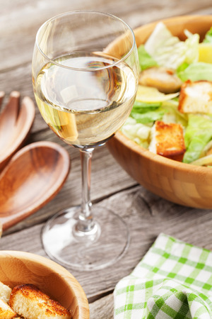 glass table: White wine glass and caesar salad on wooden table