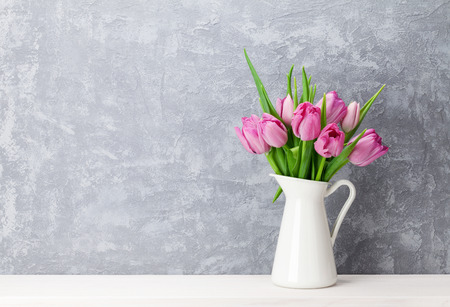 Fresh pink tulip flowers bouquet on shelf in front of stone wall. View with copy space