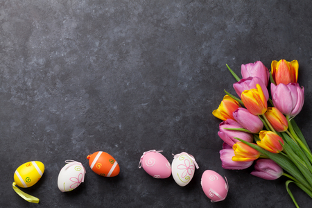 Colorful easter eggs and tulip flowers on stone table. Top view with copy space
