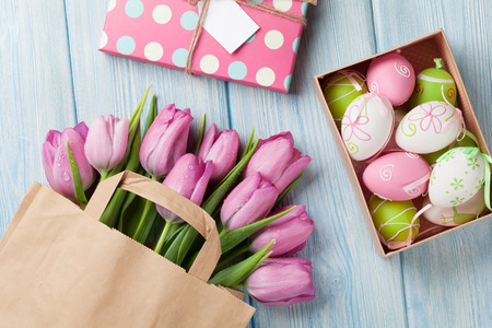 gift bags: Colorful easter eggs and tulip flowers on wooden table. Top view Stock Photo