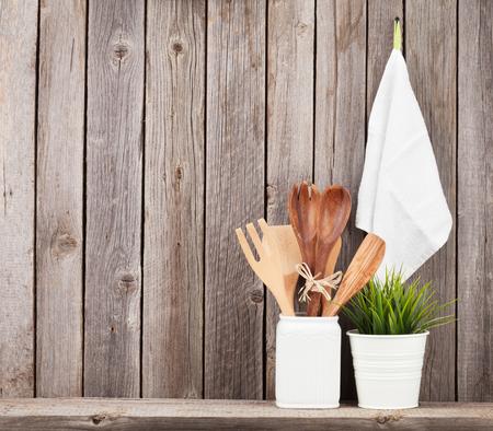 cocina antigua: Kitchen utensils on shelf against rustic wooden wall