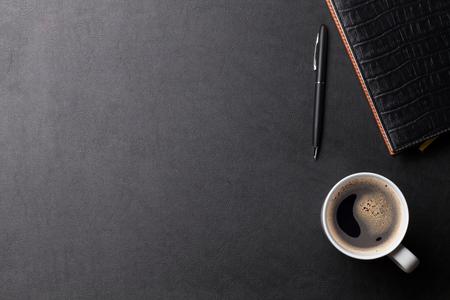 Office leather desk table with coffee and supplies. Top view with copy space