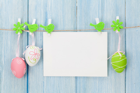 Easter greeting card and eggs in front of wooden wall