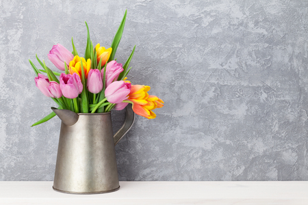 Fresh colorful tulip flowers bouquet on shelf in front of stone wall. View with copy space Foto de archivo