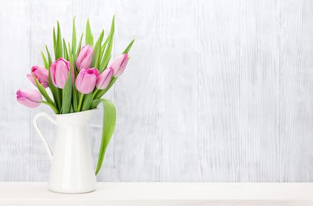 新鮮なピンクのチューリップの花ブーケ棚木製の壁の前に。コピー スペースを表示します。