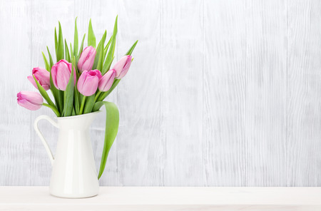 traditional gifts: Fresh pink tulip flowers bouquet on shelf in front of wooden wall. View with copy space