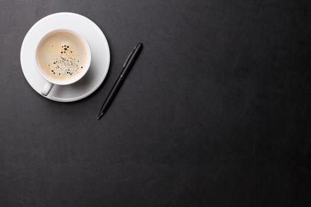 Kantoorleertafeltafel met koffiekopje en pen. Bovenaanzicht met kopie ruimte