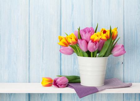 나무 벽의 앞에 선반에 신선한 화려한 튤립 꽃 꽃다발. 복사본 공간으로보기