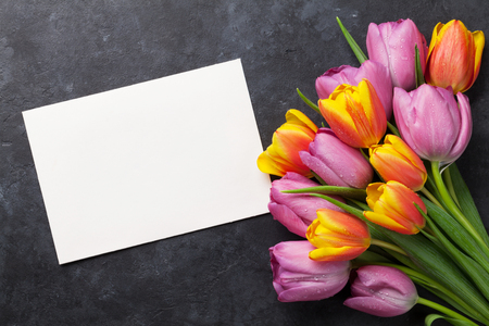dark pastel green: Fresh colorful tulip flowers and blank greeting card on dark stone table. Top view with copy space