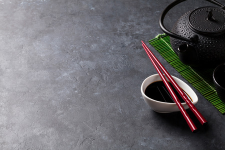 Green tea and sushi chopsticks on stone table. View with copy space
