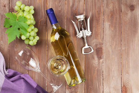 white wine: Bunch of grapes, white wine and corkscrew on wooden table background. Top view with copy space