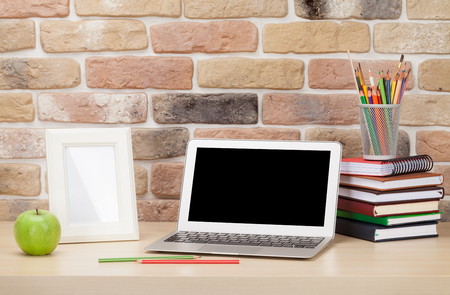 office wall: Office desk workplace with laptop and photo frame in front of brick wall. Loft style Stock Photo