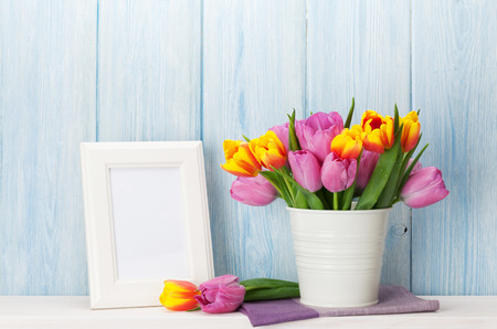 Tulips: Fresh colorful tulip flowers bouquet and blank photo frame with copy space on shelf in front of wooden wall