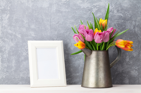 frame wall: Fresh colorful tulip flowers bouquet and blank photo frame with copy space on shelf in front of stone wall