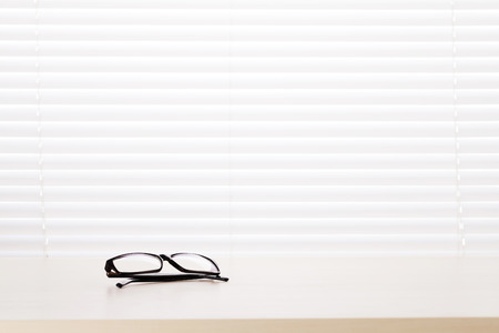 wood blinds: Office workplace with glasses on wood desk table in front of window with blinds Stock Photo