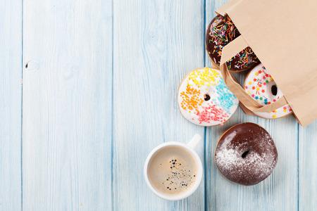 Kleurrijke donuts in een papieren zak en kopje koffie op houten tafel. Bovenaanzicht met een kopie ruimte