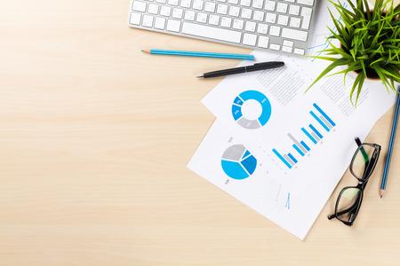 オフィス デスク職場 pc および木製のテーブル上のグラフ。コピー スペース平面図
