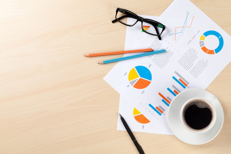 Office desk workplace with coffee cup and charts on wooden table. Top view with copy space Stockfoto