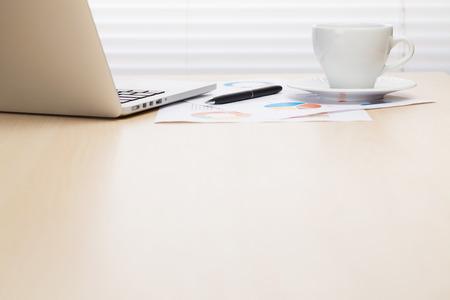 노트북 및 커피 나무 책상에 사무실 직장 블라인드 창 앞의 테이블입니다. 컵에 중점을 둡니다. 사본 공간으로보기