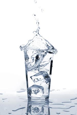 Glas water met ijs en splash. Geïsoleerd op witte achtergrond