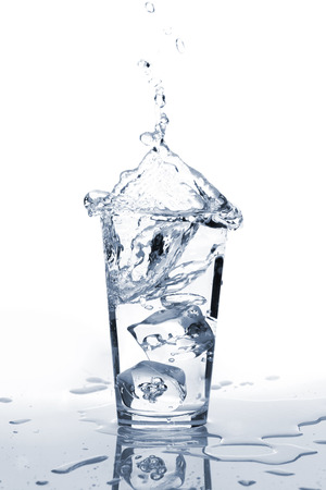 flowing water: Glass of water with ice and splash. Isolated on white background Stock Photo